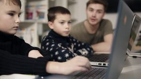 Kid`s arms typing somethingon laptop keyboard with two unrecognizable figures sitting on the background. Programmingfor. Kids class. Learning how to use stock video footage