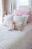 Kid's bedroom with doll on bed in pink color style Royalty Free Stock Photo