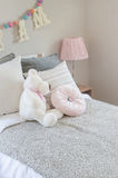 Kid's bedroom with pillows and dolls on bed Stock Photo