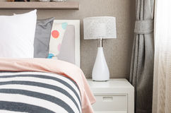 Kid's bedroom with white pillows and lamp on modern bed Royalty Free Stock Image