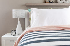 Kid's bedroom with white pillows and lamp on modern bed Royalty Free Stock Photo