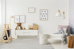 Kid`s bedroom with wooden furniture. Natural, bright kid`s bedroom interior with wooden furniture, designer accessories and posters on a white wall Stock Image