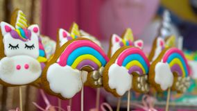 Kid`s birthday party. Unicorn themed treats, against colorful background. Slow close-up motion of delicious multicolored rainbow and unicorn cookies on stick stock video footage