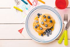 Kid`s breakfast - pancakes, blueberries and maple syrup royalty free stock images
