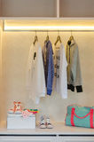 Kid's clothes hanging on rack with shoes and socks Stock Images