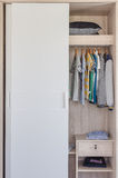 Kid's clothes hanging in white wardrobe Royalty Free Stock Image