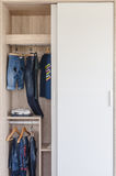 Kid's clothes hanging in white wardrobe Royalty Free Stock Images