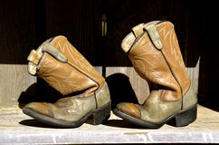 Kid's cowboy boots. A pair of worn out old kid's cowboy boots are left on a shelf royalty free stock images