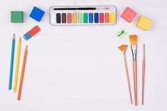 Kid`s desk with colorful pencils, brushes and watercolors, top view. With copy space royalty free stock photography