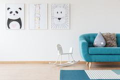 Kid`s drawings in living room. Kid`s drawings on the wall and white rocking horse in blue living room with pillows on settee and carpet Stock Images