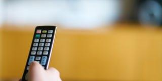 KidÂs Hand, die einen Fernsehfernprüfer hält stockfotografie