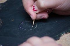 kid& x27; s hand die op een bord trekken stock foto