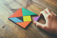 Kid's hand holding a missing piece in a square tangram puzzle, over wooden table. Stock Images