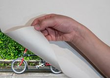 Kid`s hand open paper corner revealing bicycle with nature view. Travel concept Stock Photos