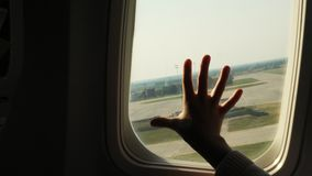 Kid s hand touching airplane window, close up. Silhouette of a child`s palm against the background of a window in an. Airplane. The concept of safety of flights stock video footage