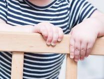 Kid's hands on a board. Kid's hands on a board on a light grey background. Closeup Stock Image