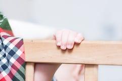 Kid's hands on a board. Kid's hands on a board on a light grey background. Closeup Stock Photo
