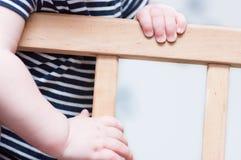 Kid's hands on a board. Kid's hands on a board on a light grey background. Closeup Stock Photos