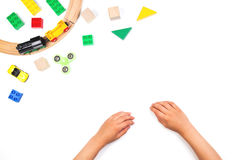 Kid`s hands and colorful toys. Fidget spinner, cars, toy train, bricks and blocks on white background Royalty Free Stock Photography