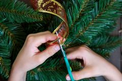 Kid`s hands cut red ribbon for decoration of the wreath on the wooden background stock photo