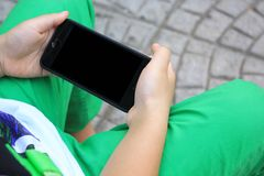 Kid`s hands hold smart phone for playing and education stock photo