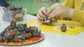Kid`s hands molded plasticine figurines stock video