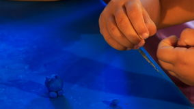 Kid's hands sculpture toy animal of blue stock video