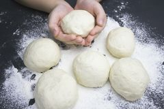 Kid`s hands, some flour an wheat dough on the black table. Children hands making the rye dough for backing bread or pizza. Small. Hands with dough. Little child royalty free stock images