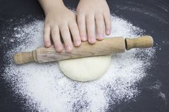 Kid`s hands, some flour, wheat dough and rolling pin on the black table. Children hands making the rye dough for backing bread. Small hands kneading dough stock image