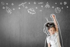 Kid`s learning inspiration in science education with girl child`s imagination doodle on teacher`s school chalkboard for back to sc
