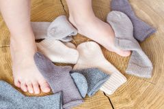 Kid& x27;s leg in a heap of cute small different colored cashmere knitted newborn baby socks on a wooden desk background royalty free stock photography