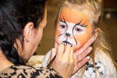 Kid's make-up. Mother is preparing make-up for her daughter for a party royalty free stock images