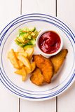 Kid`s meal  - fried chicken strips, french fries, salad and ketchup. Colorful dinner on white wooden table. Plate captured from above top view, flat lay royalty free stock photos