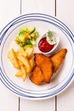 Kid`s meal  - fried chicken strips, french fries, salad and ketchup. Colorful dinner on white wooden table. Plate captured from above top view, flat lay royalty free stock image