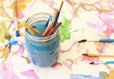 Paint brushes soaking in a glass jar of soapy water Stock Images