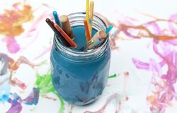 Paint brushes soaking in a glass jar of soapy water Stock Photos
