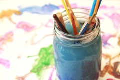 Paint brushes soaking in a glass jar of soapy water Stock Photography
