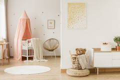 Kid`s open space interior. Gold poster in kid`s open space interior with canopied cradle and teddy bear in a basket on pouf stock photography
