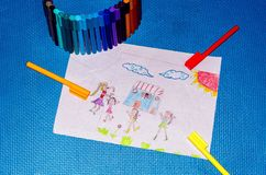 Kid`s painting and Crayons on blue background royalty free stock image