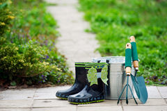 Kid's rain boots and garden tools Stock Images