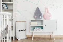 Kid`s room with paper bag. Pink and grey pillow on white cupboard in kid`s room with paper bag and shelf against triangles wall stock photos