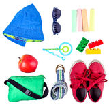 Kid's street outfit and some toys on white background. Isolated. Overhead view royalty free stock photo