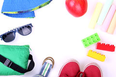 Kid's street outfit and some toys on white background. Overhead view. Place for your text. Frame style. Partly isolated with shadows royalty free stock image