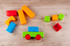 Kid`s toys. Different color plastic blocks on wooden table Royalty Free Stock Images