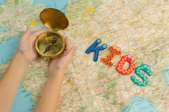Kid`s travel theme background. Kid hands holding gold compass under map. Royalty Free Stock Photography
