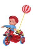 Kid's wind-up retro toy. Little plastic boy, holding a balloon, riding a tin trike, with a bell on the back, isolated against white ground royalty free stock images