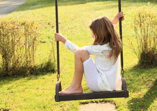 Kid - sad girl on swing. Barefoot kid - sad girl in white clothes sitting and swinging on a swing Royalty Free Stock Photography