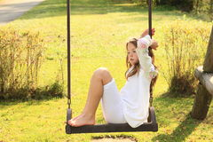 Kid - sad girl on swing. Barefoot kid - sad girl in white clothes sitting and swinging on a swing Stock Photography