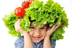 Kid with salad and tomato hat on his head stock images
