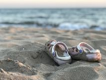 Kid sand beach slippers on the beach. In the sunset royalty free stock photo